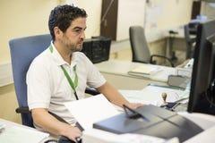 Medelålders man som arbetar på hans kontor genom att använda datoren arkivfoton