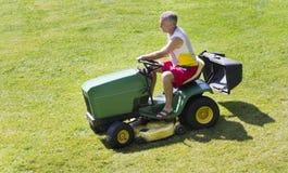 Medelålders man som mejar gräsmatta på ridninggräsklippningsmaskinen arkivbilder