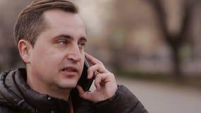 Medelålders man som talar på den utomhus- telefonen stock video