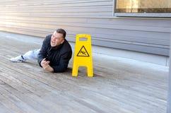 Medelålders man som tas en nedgång på ett halt golv arkivfoto