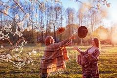 Medelålders moder och hennes vuxen dotter som kastar hattar i blommande trädgård Fostra dagbegreppet för ` s gyckel som har kvinn Arkivfoton