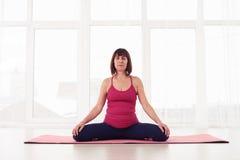 Medelålders yogini som in kopplar av och mediterar under yogagrupp Royaltyfria Foton