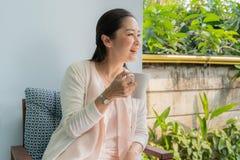 Medelåldersa asiatiska kvinnor att sitta och läppja kaffe royaltyfria bilder