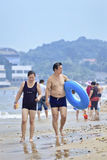 Medelåldersa kinesiska par går på stranden i Yantai, Kina Royaltyfria Foton
