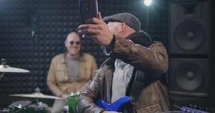 Medelåldersa musiker som gör selfies i studio arkivfilmer