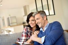 Medelåldersa par som kopplar av i soffa arkivbild