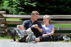 Medelåldersa par som tar ett avbrott, medan rollerblading ut Fotografering för Bildbyråer