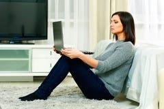 Medelålderst härligt kvinnasammanträde på golvet och användabärbara datorn Royaltyfri Bild