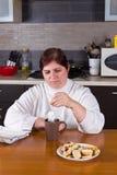 Medelålderst kvinnadanandete i kök Royaltyfri Foto