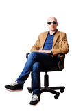 Medelålderst mansammanträde i en kontorsstol arkivfoto
