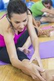 Medelåldrig kvinna som sträcker övande Yoga Royaltyfri Bild