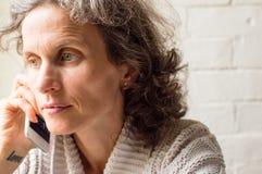 Medelåldrig kvinna som talar på telefonen Fotografering för Bildbyråer
