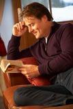 Medelåldrig man som kopplar av med boken som sitter på sofaen Arkivfoton