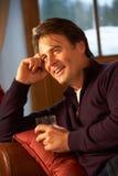 Medelåldrig man som kopplar av på dricka Whisky för Sofa Arkivbild