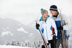 Medelåldriga par skidar på ferie i berg royaltyfri bild