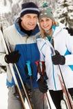 Medelåldriga par skidar på ferie i berg Arkivfoton