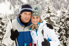 Medelåldriga par skidar på ferie i berg Royaltyfri Foto