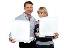 Medelåldriga par som rymmer vita pizzaaskar arkivfoton