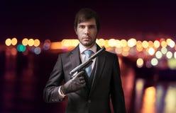 Medel eller spion med vapnet på natten vägg för skugga för pistol för holding för brotts- främre hand för tegelstenbegrepp hård Royaltyfria Bilder