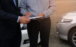 Medel för försäkring för förlustregulator Inspecting Damaged Car Arkivbilder