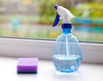 medel som tvättar fönster Flaska av sprej och en svamp closeup Royaltyfri Foto