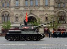 Medelbehållaren t-34-85 med det röda banret på röd fyrkant under en repetition av ståta Arkivbild
