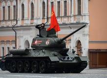 Medelbehållaren t-34-85 med det röda banret på röd fyrkant under en repetition av ståta Royaltyfri Fotografi