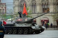 Medelbehållaren t-34-85 med det röda banret på röd fyrkant under en repetition av ståta Royaltyfri Bild