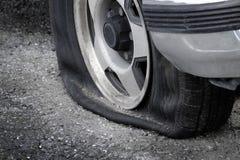 Medelbil för plant gummihjul på farligt strandsatt för vägfara royaltyfria foton