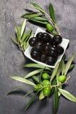 Medelhavs- gräsplan och svarta oliv över den mörka stenen Royaltyfria Foton