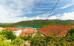 Medelhavs- hus med röda tak och Adriatiskt havet i bakgrunden, Dalmatia, Kroatien Arkivfoton