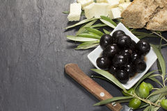 Medelhavs- oliv med fetaost, olje- och nytt bröd för jungfrulig extrahjälp över den mörka stenen Royaltyfri Bild