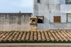 Medelhavs--täckt tak som är främst av fula fasader av de bakre byggnaderna royaltyfri bild