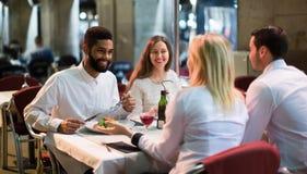 Medelklassfolk som tycker om mat i kaféterrass Fotografering för Bildbyråer