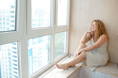 Medelålders kvinna nära fönster Royaltyfria Foton