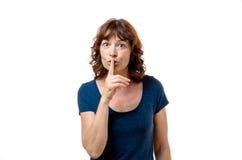 Medelålders kvinna som gör en hyssja ner gest Fotografering för Bildbyråer