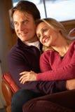 Medelåldriga par som pratar på sofaen i Chalet Royaltyfri Fotografi