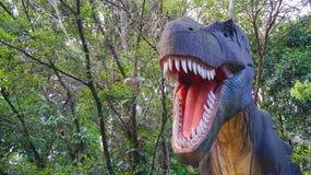 Medellin, Antioquia/Colômbia - 11 de novembro de 2015: Tiranossauro Rex da escultura com um fundo das árvores em um parque de div Imagem de Stock