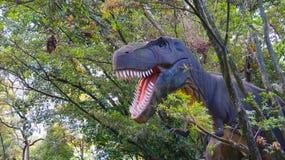 Medellin, Antioquia/Colômbia - 11 de novembro de 2015: Tiranossauro Rex da escultura com um fundo das árvores em um parque de div Foto de Stock