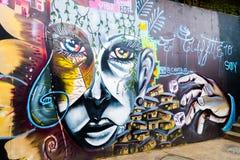 MEDELLIN COLOMBIA OKTOBER 22, 2017: Väggen täckte vid grafitti i gatorna av grannskapen för comuna 13 i Medellin Royaltyfri Foto
