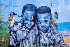 MEDELLIN, KOLUMBIA PAŹDZIERNIK 22, 2017: Ściana zakrywał graffiti w ulicach comuna 13 sąsiedztwo w Medellin Fotografia Royalty Free
