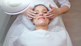 Medelnärbild som ler den Caucasian unga kvinnan som tycker om ansikts- massage på cosmetologistkliniken arkivfilmer