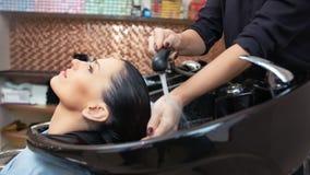 Medelnärbild som ler den charmiga kvinnaklienten under tvättande hår på friseringsalongen arkivfilmer