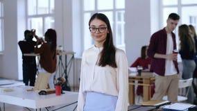 Medelskjuten stående av den positiva millennial brunettaffärskvinnan i glasögon som ler på kameran på det moderna kontoret stock video