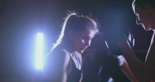Medelskott av härliga kardor för fokus för hastighet för slag för treneruemsya för konditionkvinnaboxare med en lagledare i en bo lager videofilmer