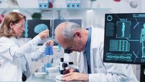 Medelskott av mogna forskare som arbetar i upptaget laboratorium lager videofilmer