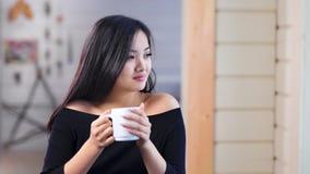 Medelskott som ler den förtjusande asiatiska unga kvinnan som drömmer och tycker om dricka kaffe eller te lager videofilmer