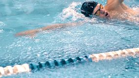 Medelslut upp torson av den idrotts- unga simmaren som utför krypandestil i simbassäng arkivfilmer