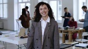 Medelstående av den unga Caucasian affärskvinnan med lockigt hår, formellt le för dräkt som är lyckligt på kameran på det moderna lager videofilmer