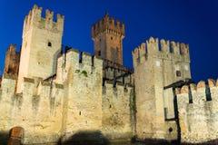 Medeltida befästningScaliger slott på natten i Sirmione, Italien Royaltyfri Foto